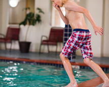 a boy jumping into an indoor pool