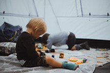 boys playing with toys in a tent
