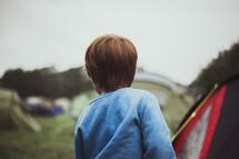 a boy standing near tents