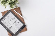 Bible study notes on a tablet and leather journal