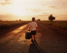 a boy standing in the middle of a rural road holding a suitcase