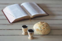 open Bible and communion bread and wine