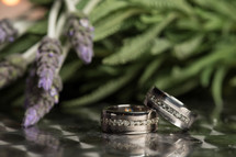 Two diamond wedding bands near some lavender.