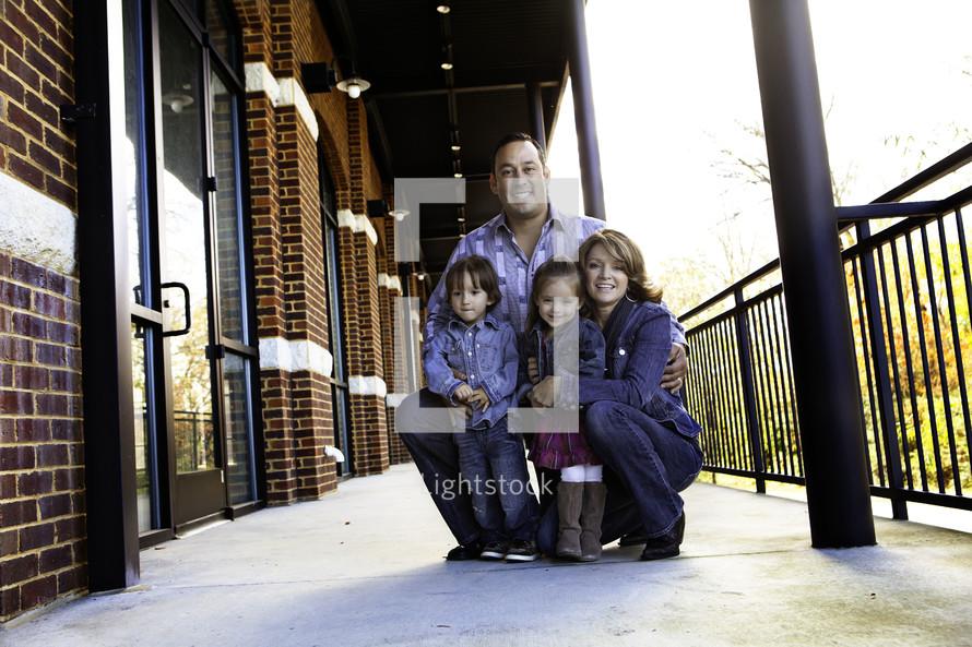 family squatting on sidewalk of street