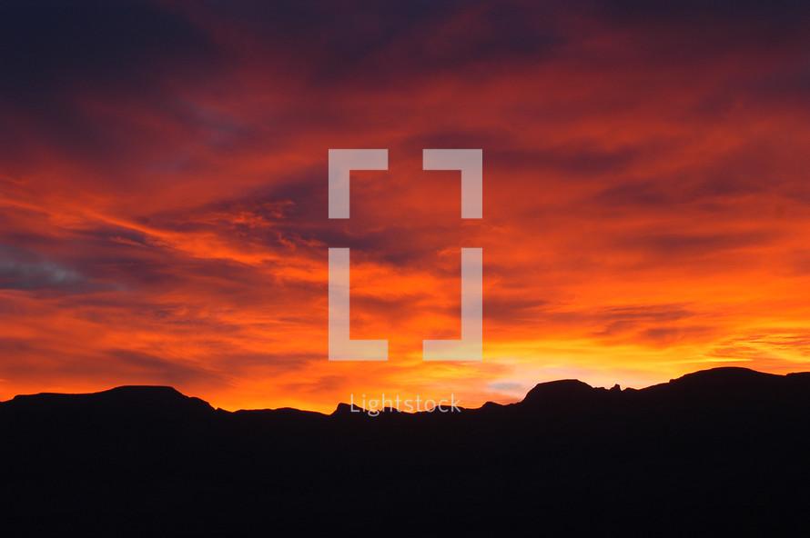 Sunrise through cloudy orange red sky