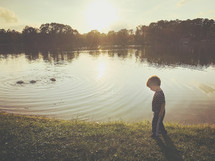 a toddler boy walking by a pond