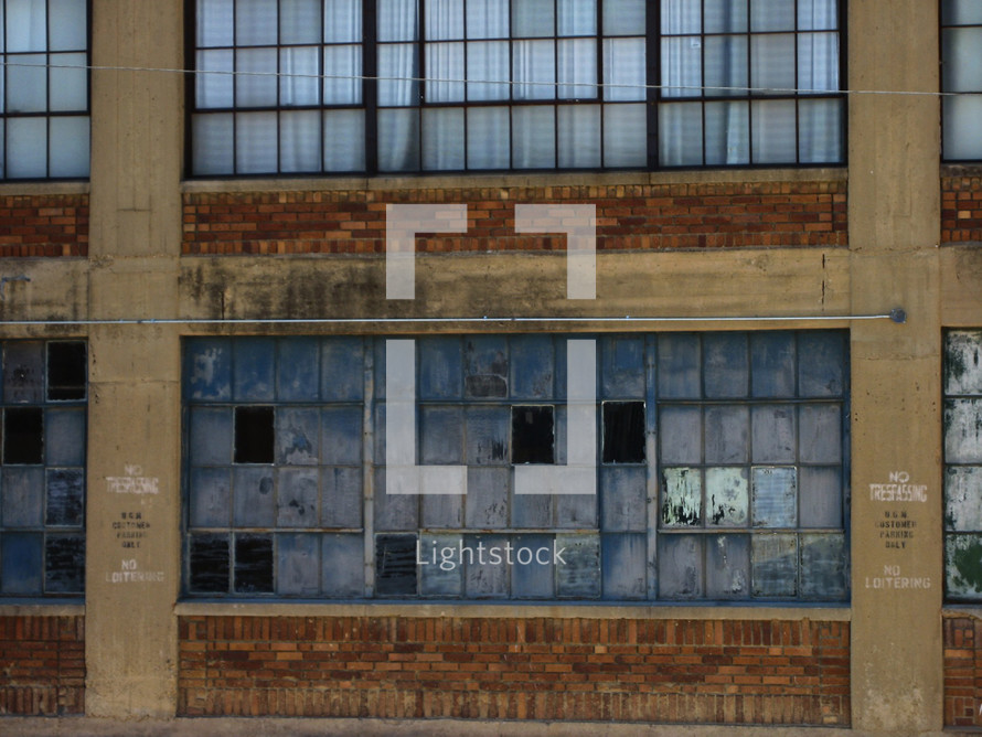 Abandoned brick and cement building with broken windows
