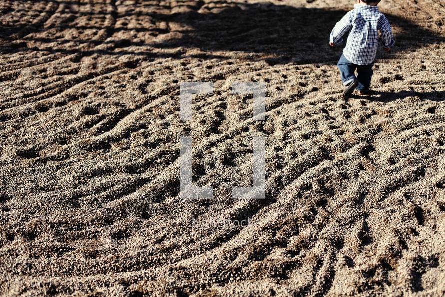Boy running through gravel