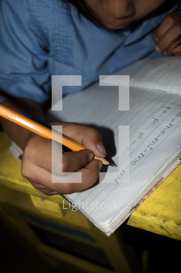 Child writing on notebook paper in a classroom in Honduras