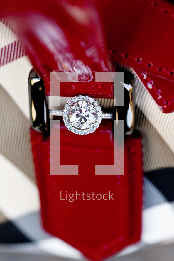 Diamond engagement ring hidden in red leather strap buckle wedding bride round