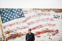 man standing in front of an American Flag painted on a brick wall