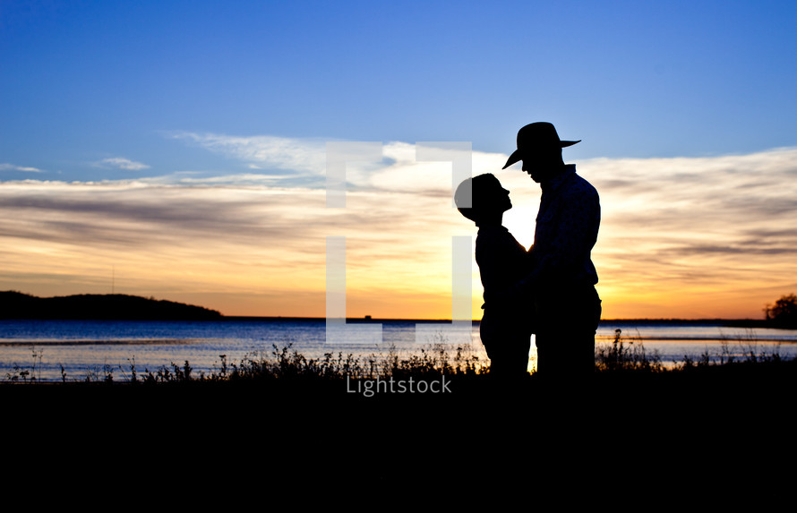 silhouette of a woman and man ln a cowboy hat