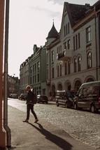 a man walking down a sidewalk along side a cobblestone street