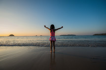 a girl standing on a tropical beach with arms raised