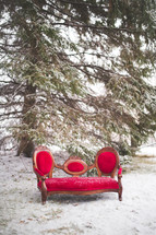 a red couch outdoors in the snow