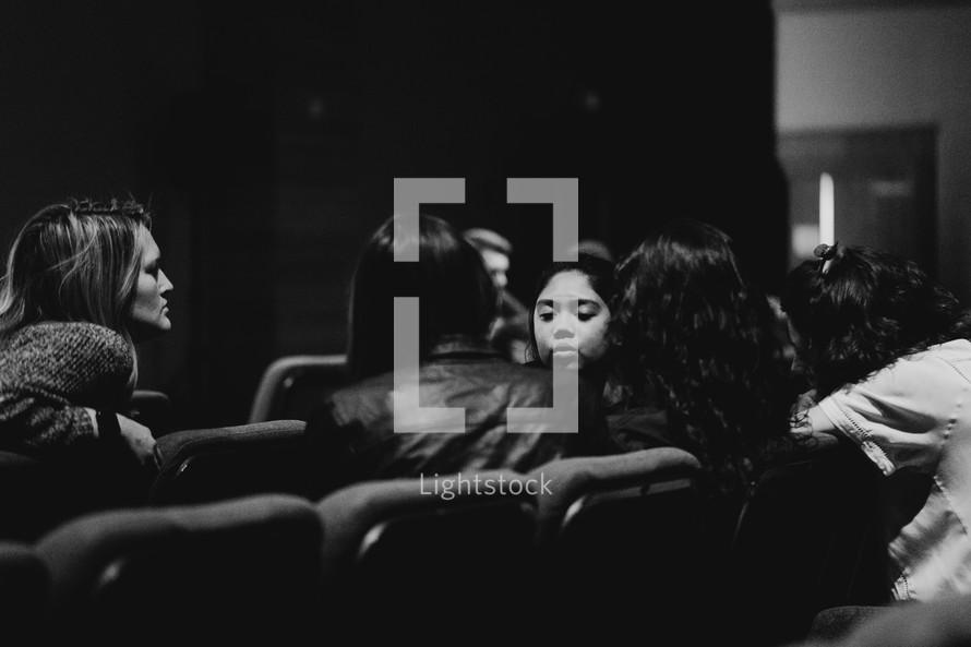 women talking in auditorium seats