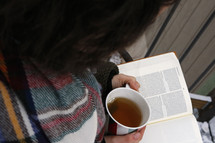 a woman reading a Bible with tea