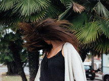 a woman flipping her hair under palm trees