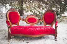 a red couch in the snow outdoors
