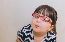 face of a girl child in reading glasses