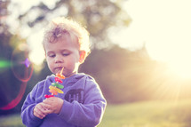 A little boy eating candy on a stick while outdoors.