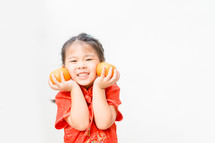 a little girl in traditional Chinese dress holding oranges