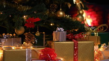 Christmas gifts near Christmas tree in atmospheric lights in front of fireplace. Dolly shot
