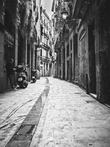 A man texting next to a scooter in a narrow alley in Barcelona