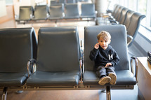 a boy child in a waiting area playing on a cellphone