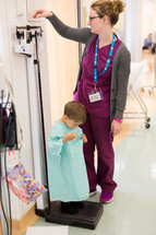 a nurse weighing a boy child in a hospital gown