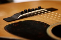 pick guard, bridge, and saddle of an acoustic guitar