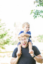 father carrying his toddler son on his shoulders