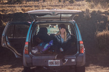 a woman sitting in the back of an SUV with the tailgate up