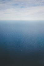The wake of a boat in the vast ocean water as it meets the sky on the horizon.