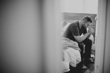 Man with head bowed, sitting on side of bed praying.