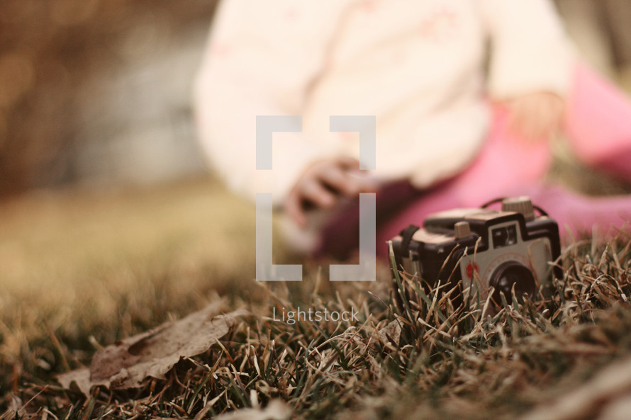 Toddler sitting in grass reaching for camera.