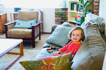a child sitting on a couch playing with toy cars