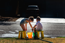 kids filling buckets with water from a hose