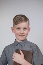 a smiling boy child holding a Bible close to his chest