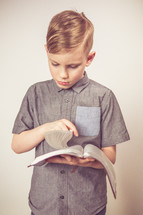 boy child standing reading a Bible
