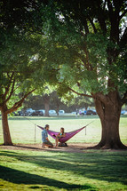 man down on his knees proposing to a woman in a hammock