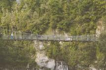 A pedestrian suspension bridge over a gorge.