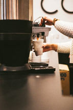 A woman getting a cup of coffee from a coffee machine.