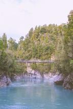 A pedestrian suspension bridge over a river.