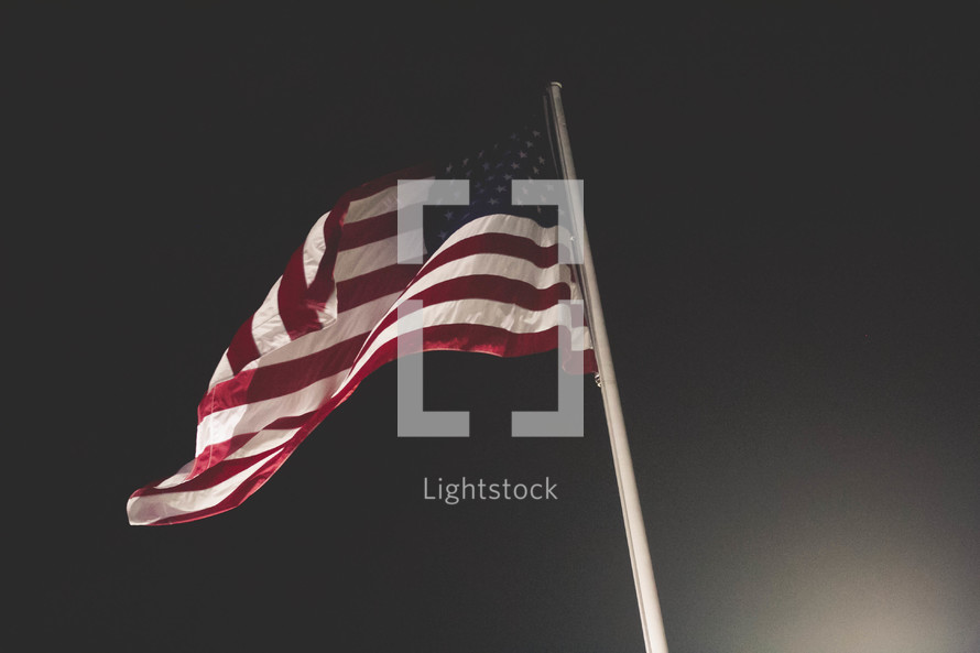 American flag on a flagpole at night