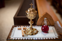 chalice, cross and holy water on table