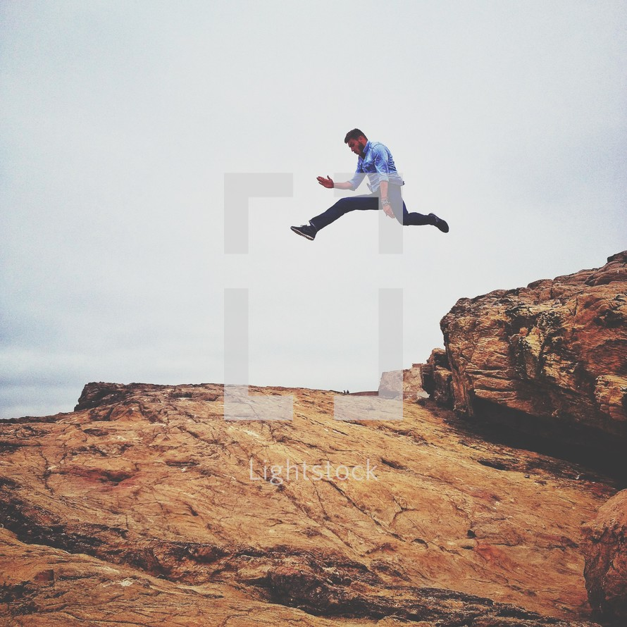 Man jumping from rock in midair
