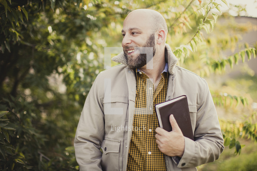 man holding a Bible outdoors