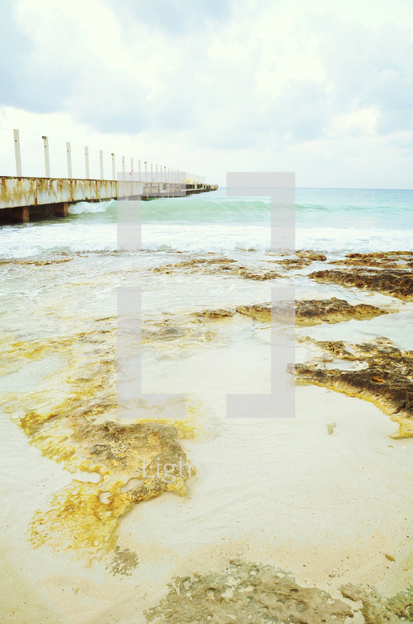 Water and mud flowing onto wet beach with pier and clouds in the background.