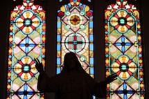 silhouette of a statue of Jesus in front of stained glass windows